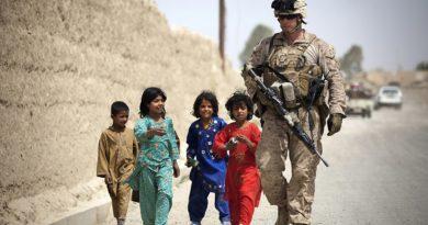 Gruppe afghanischer Kinder mit American Marine auf Streifendienst zu Fuß